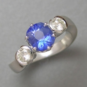 Other Rings 1-6: Oval blue sapphire in prongs with round partial bezel set diamonds in a white gold setting with a twist