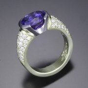Other Rings 2-1: Oval tanzanite in a partial bezel with pave set diamonds in platinum