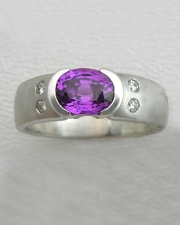 Other Rings 3-10: Oval purple sapphire in a partial bezel with flush set diamonds on the sides in white gold