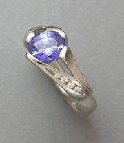 Other Rings 3-11: Oval blue sapphire in a stylized prong setting with channel set diamonds in white gold