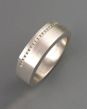 Bands 3-5: Small diamonds channel set across the top of a squared white gold band