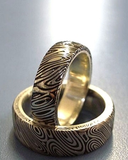Oxidized Damascus Stainless Steel wedding set lined in 18k Yellow gold