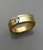 Round cut blue sapphire bezel set in yellow gold with a recessed textured platinum inlay