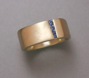 14k Yellow gold square shaped band with tapered offset channel of Round Blue Sapphires