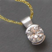 Necklace 1-9: Round cut diamond in a partial bezel in white gold