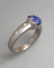 1-10: Round blue sapphire partial bezel set in platinum with small scattered flush set diamonds
