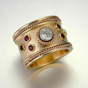 Engagement Ring 2-1: Round cut diamond in platinum full bezel set in yellow gold with full bezel set garnets