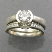 Engagement Ring 2-5: Round cut diamond partial bezel set in white gold with diamonds on the side shown with channel set diamond band
