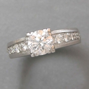 Engagement Ring 4-11: Round cut diamond square prong set in platinum with bead set diamonds on the sides