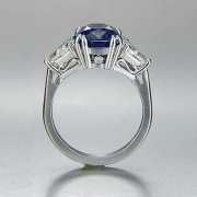 Engagement Ring 5-1: Cushion cut blue sapphire prong set in platinum with triangular diamonds on the sides