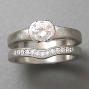 Engagement Ring 5-11: Round cut diamond partial bezel set in white gold shown with matching curved bead set diamond band