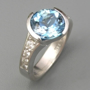Engagement Ring 5-7: Round cut Aquamarine partial bezel set at an angle in white gold with bead set diamonds on the sides
