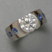 Engagement Ring 6-1: Round cut diamond partial bezel set in platinum with flush set blue sapphires on the sides