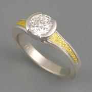 Engagement Ring 6-3: Round cut diamond partial bezel set with 24karat gold on the sides