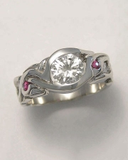 Engagement Ring 6-4: Round cut diamond partial bezel set in white gold with rubies and diamonds on the sides