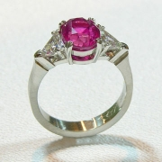 Engagement Ring 6-6: Oval cut pink sapphire prong set in platinum with triangular diamonds on the sides