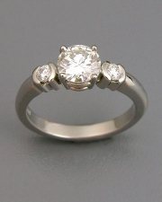 Engagement Ring 6-8: Round cut diamond prong set in white gold with partial bezel set diamonds on sides