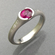 Engagement Ring 7-11: Round cut pink sapphire partial bezel set in white gold with flush set diamonds on the sides