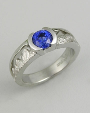 Engagement Ring 7-6: Round cut blue sapphire partial bezel set in platinum with mountains on the sides