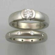 Engagement Ring 7-7: Round cut diamond partial bezel set in white gold shown with flush set diamond band