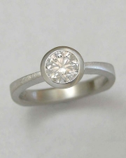 Engagement Ring 9-7: Platinum engagement ring with round center diamond set in a full bezel